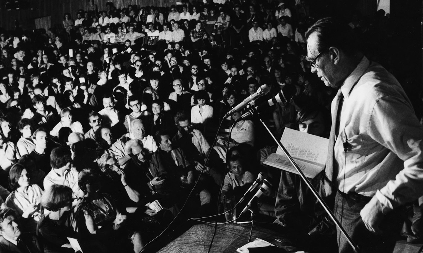 <p>Poet and Nobel Prize winner Czesław Miłosz speaking onstage to a crowd of students at Warsaw University, Poland, 1981. <em>Photo by Keystone/Getty</em></p>