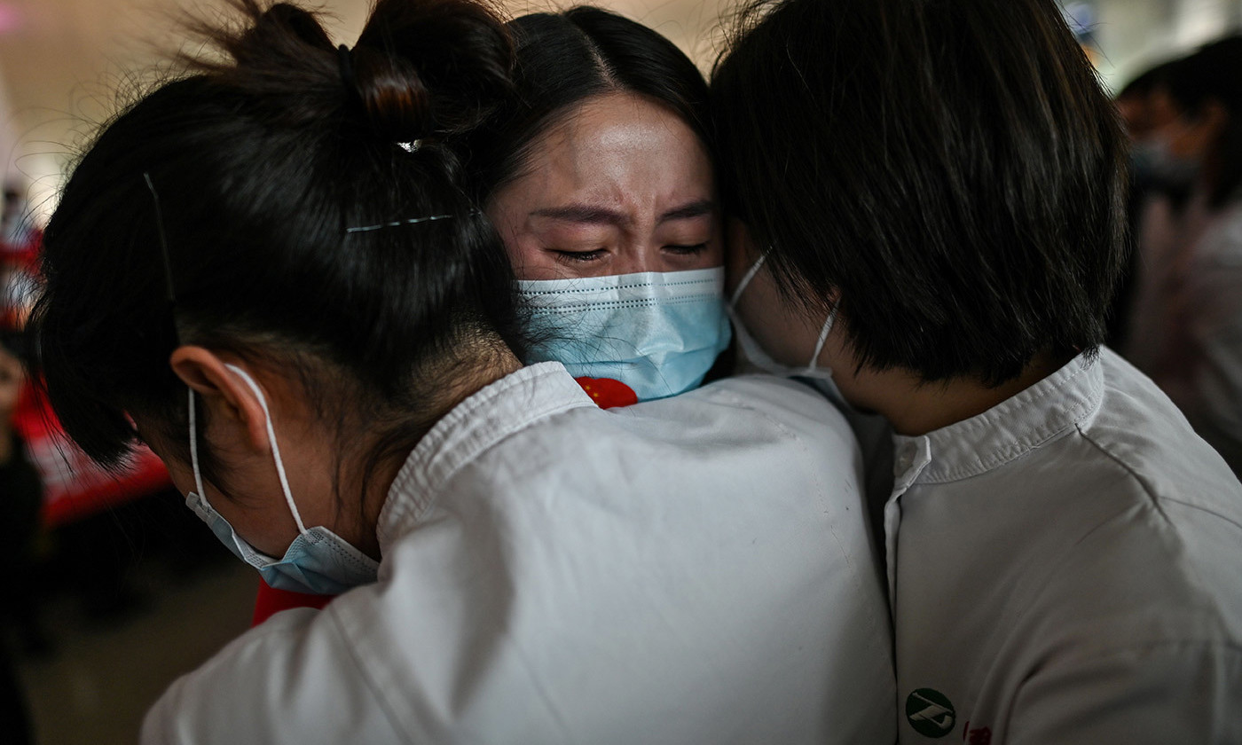 <p>Medical workers in Wuhan embrace. 8 April 2020. <em>Photo by Hector Retamal/AFP/Getty</em></p>