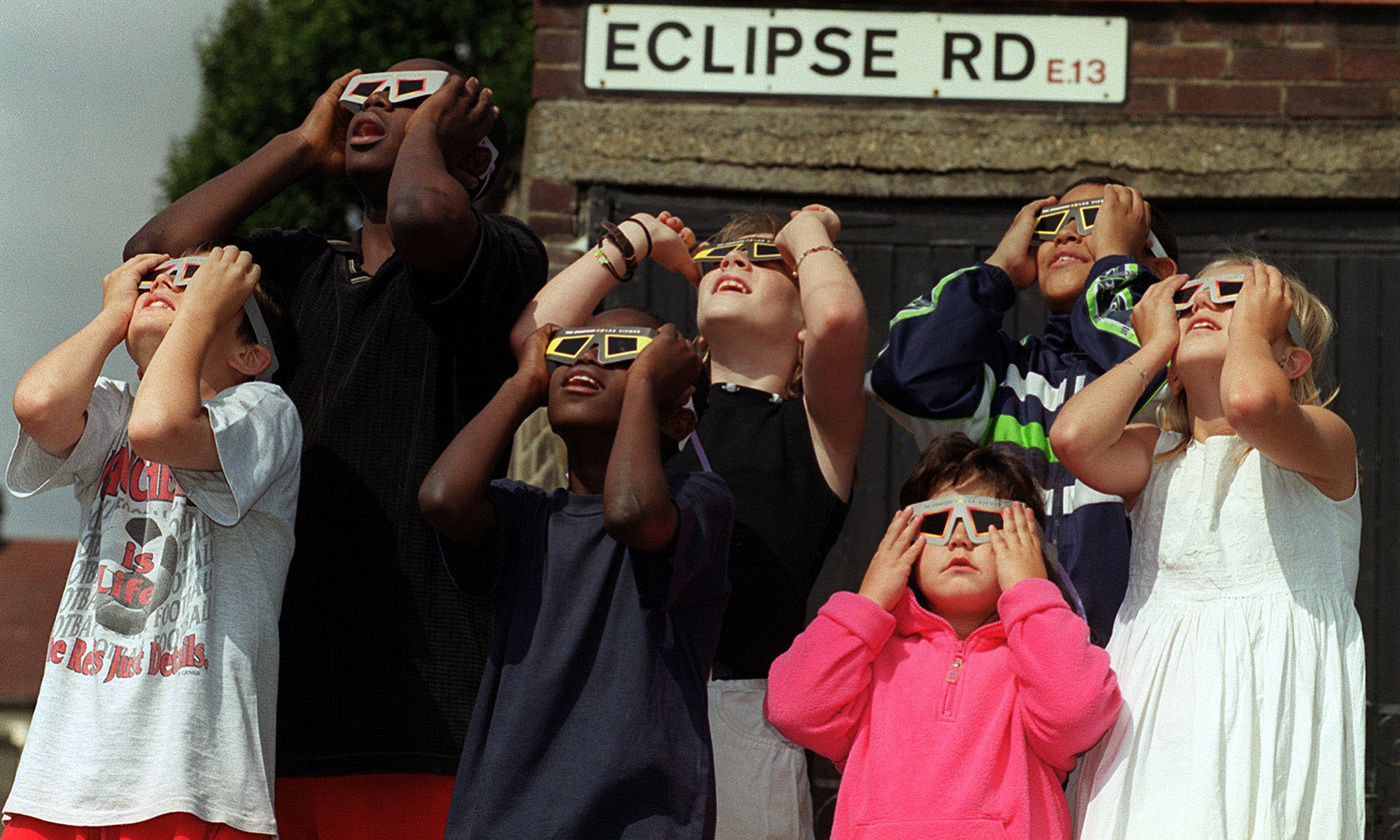<p>Children gather in a London street to watch the 1999 total solar eclipse. <em>Photo by Fiona Hanson/PA/Getty</em></p>