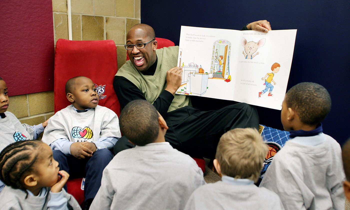 Mike Brown, former head coach of the Cleveland Cavaliers, reads to children at the Cavaliers All-Star Library at the Kenneth Clement Boys Leadership Academy, 12 February 2008. <em>Photo by David Liam Kyle/Getty</em>