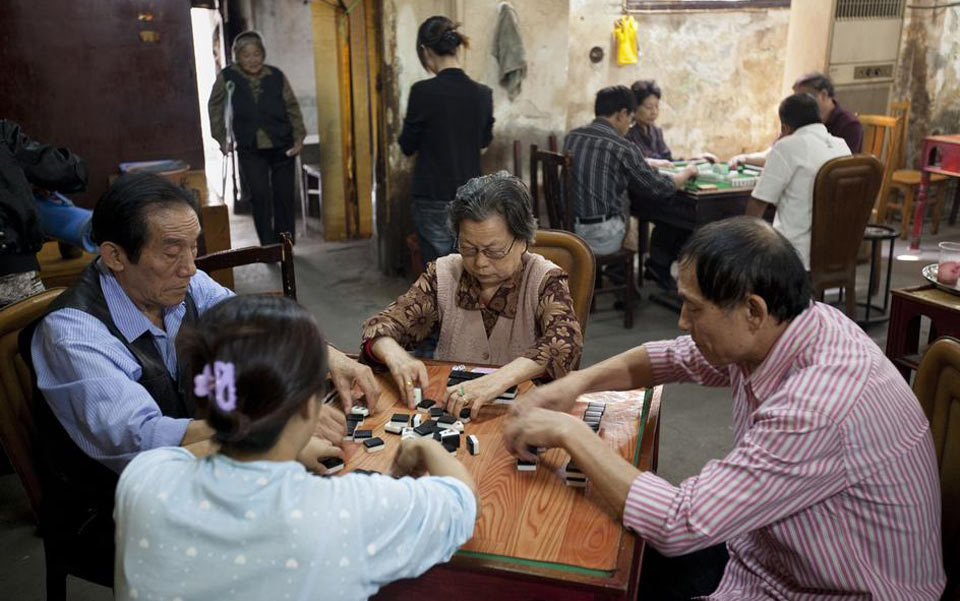 Older Chinese men and women enjoy a game of Mah Jong